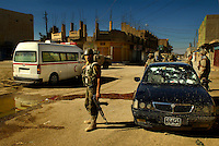 After shooting a fleeing insurgent's vehicle, members of the Iraqi army, 4th Battalion, 2nd Brigade, 5th Division, provide medical assistance to the car's occupants during an operation in Old Baqubah, Iraq, on March 11, 2007. The purpose of the operation is to eliminate Old Baqubah as an operating base for improvised explosive device building cells and key leaders of anti-Iraqi forces in Iraq.   (U.S. Air Force photo by Staff Sgt. Stacy L. Pearsall) (Released)