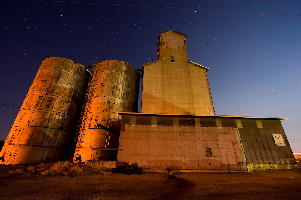 The old grain elevator at Ashkum, IL stands silent on this late night, underneath many constellations and stars overhead in the dark prairie sky.