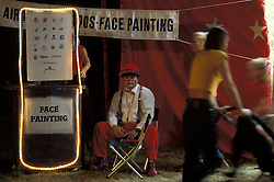"Clown offers face painting to circus visitors.  Bentley Bros. circus, one of the few remaining ""mud show"" circus performing under a canvas big top."