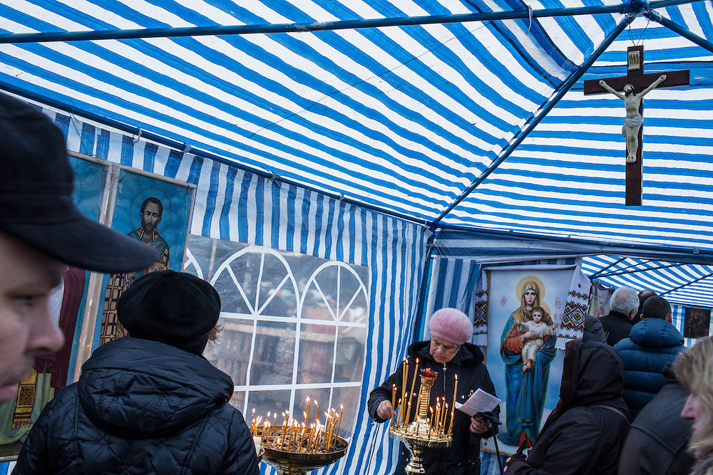 KIEV, UKRAINE - FEBRUARY 23: Women light candles in a tent serving as a chapel on Independence Square on February 23, 2014 in Kiev, Ukraine. After a chaotic and violent week, Viktor Yanukovych has been ousted as President as the Ukrainian parliament moves forward with scheduling new elections and establishing a caretaker government. (Photo by Brendan Hoffman/Getty Images) *** Local Caption ***