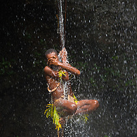 SNew Guinea man from the Jebo tribe swinging from a rope in the Jebo Falls area.