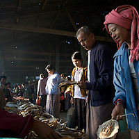 A woman bargains for some small stingrays at the daily market in Mrauk U, Myanmar.