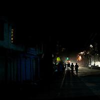 People walk along the street at night in Kargil, Jammu and Kashmir, India