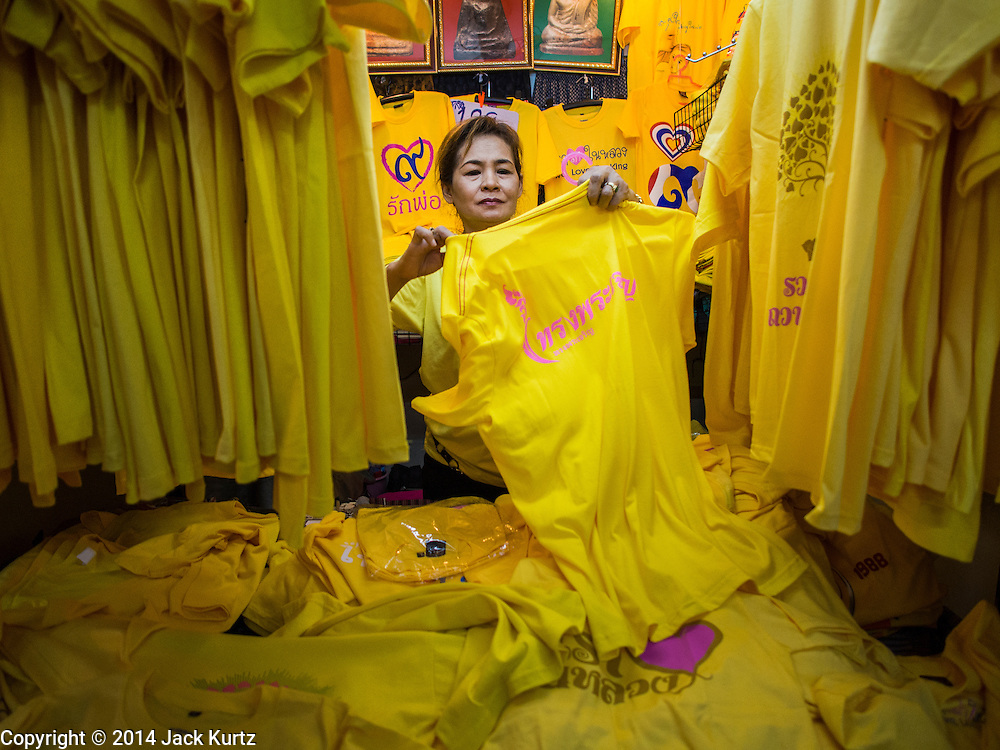 28 NOVEMBER 2014 - BANGKOK, THAILAND: A vendor in Bangkok sets up her booth selling yellow tee shirts for the King's Birthday in Thailand. Bhumibol Adulyadej, the King of Thailand, was born on December 5, 1927, in Cambridge, Massachusetts. The family was in the United States because his father, Prince Mahidol, was studying Public Health at Harvard University. He has reigned since 1946 and is the world's currently reigning longest serving monarch and the longest serving monarch in Thai history. Bhumibol, who is in poor health, is revered by the Thai people. His birthday is a national holiday and is also celebrated as Father's Day. He is currently hospitalized in Siriraj Hospital, recovering from a series of health setbacks. Thousands of people come to the hospital every day to sign get well cards for the King. People wear yellow at events associated with the King because he was born on a Monday, and yellow is Monday's color in Thai culture. It's also the color of the monarchy.       PHOTO BY JACK KURTZ
