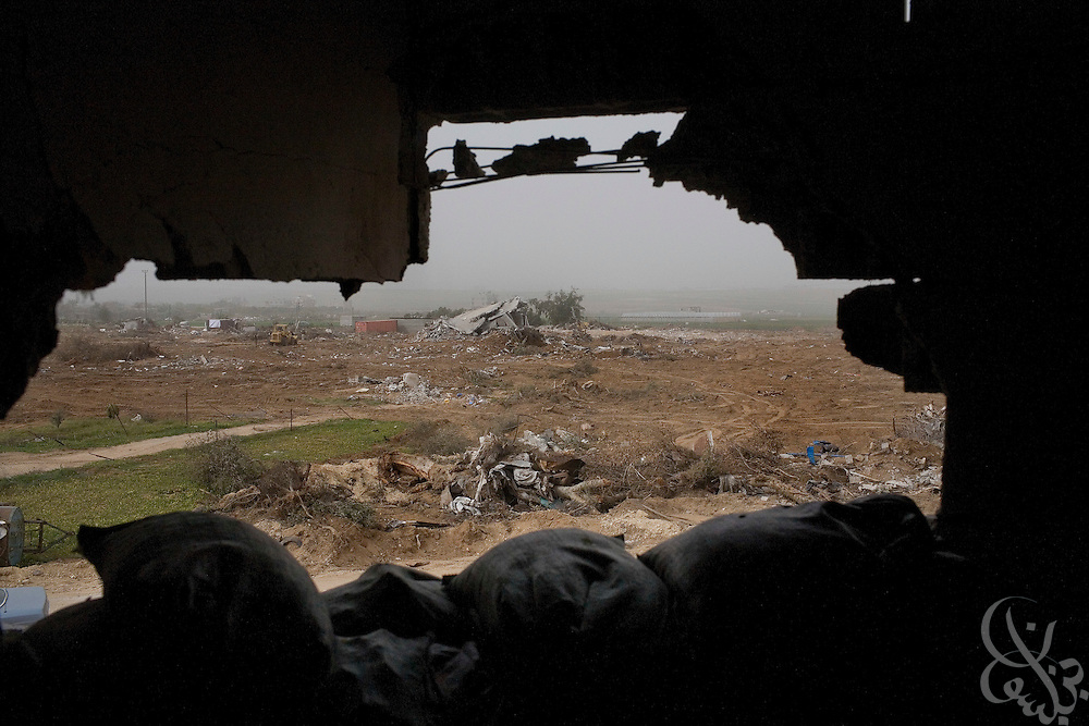 The destroyed village of Juhor al-Dik is visible through a sandbagged Israeli infantry position inside a Palestinian house used by Israeli Defense Forces during the recent 22 day operation inside Gaza January 24, 2009. From the graffiti left behind on the walls of Palestinian homes, along with food wrappers, Israeli newspapers and sandbag sniper positions, it is apparent that Israeli infantry units occupied the homes of many Palestinians  during the operation.