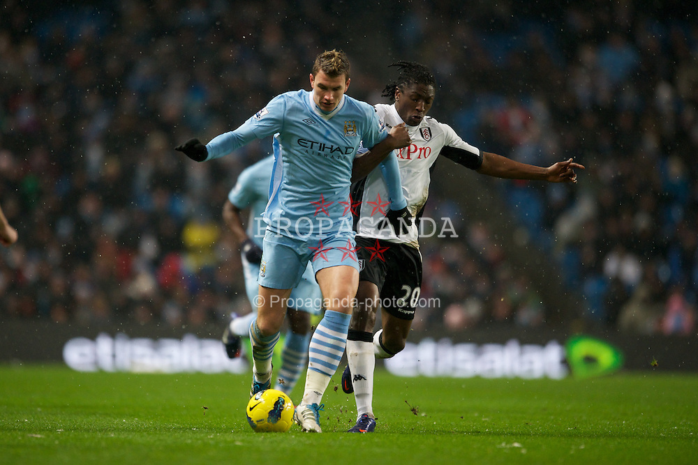 LONDON, ENGLAND - Sunday, February 04, 2012: Manchester City's Edin Dzeko in action against Fulham's Dickson Etuhu during the Premiership match at the Etihad Stadium. (Pic by Chris Brunskill/Propaganda)