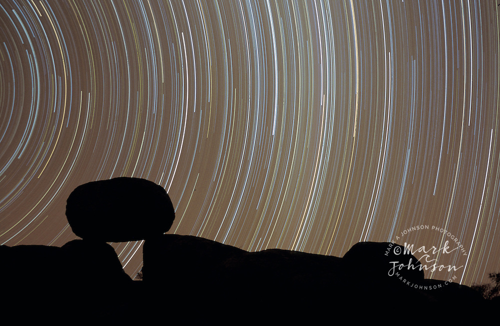 Australia, Northern Territory, Devil's Marbles at night with long exposure star trails