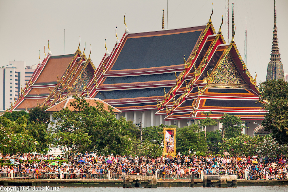 06 NOVEMBER 2012 - BANGKOK, THAILAND:  Members of the public gather underneath a portrait of Bhumibol Adulyadej, the King of Thailand, with Wat Po's roofline in the background, while they wait for the Royal Barge Procession rehearsal to begin. Thailand's Royal Barge Procession has both religious and royal significance. The tradition is nearly 700 years old. The Royal Barge Procession takes place rarely, typically coinciding with only the most important cultural and religious events. During the reign of King Bhumibol Adulyadej, spanning over 60 years, the Procession has only occurred 16 times. The Royal Barge Procession consists of 52 barges: 51 historical Barges, and the Royal Barge, the Narai Song Suban, which King Rama IX built in 1994. It is the only Barge built during King Bhumibol's reign. These barges are manned by 2,082 oarsmen. The Procession proceeds down the Chao Phraya River, from the Wasukri Royal Landing Place in Bangkok, passes the Grand Palace complex and ends at Wat Arun. Tuesday's dress rehearsal was the final practice for the 2012 Royal Barge Procession, which takes place November 9.    PHOTO BY JACK KURTZ