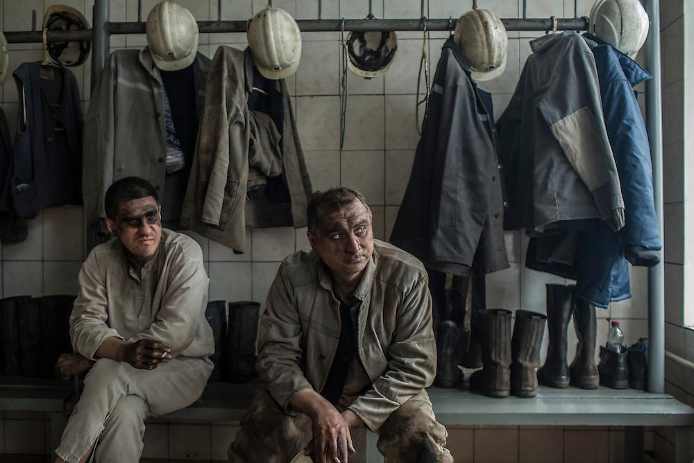 Miners smoke cigarettes after going underground at the Shcheglovskaya Coal Mine on Friday, March 25, 2016 in Makiivka, Ukraine.