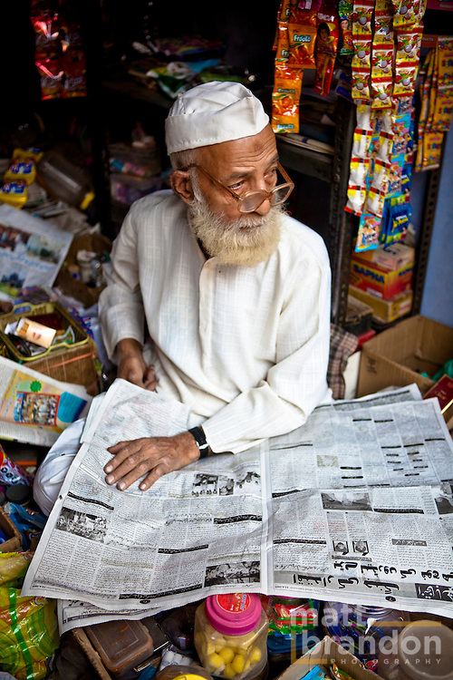 An elderly Muslim man read his newspaper while waiting for customers for his shop.