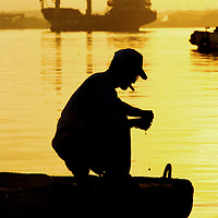 A fisherman puts bait on a line at dawn in Havana.