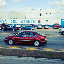 Cars pass on Mexico's Highway 307, through the town of Playa Del Carmen, MX. This is one of the fastest growing cities in North America, with the tourist industry booming in the tropical climate.