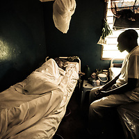 A son sits by the bed of his ailing father in a clinic in Mbuji-Mayi, DRC.