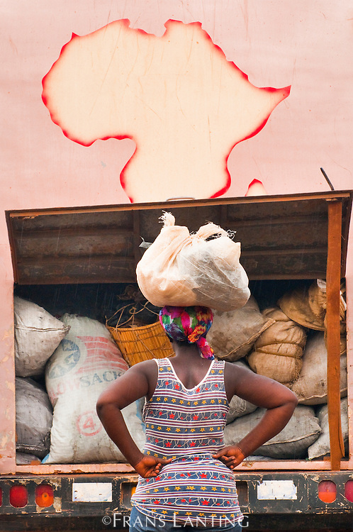 Woman carrying produce in front of bus loaded with merchandise, Wechiau, Ghana