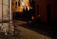 Cuban kids walk through alley during the golden hour.