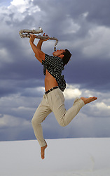 man with a saxophone in midair outdoors