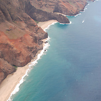 Aerial view taken from a helicopter of part of the coastline in Hawaii showing cliffs and isolated beaches