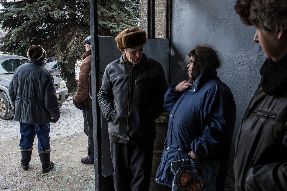 DEBALTSEVE, UKRAINE - FEBRUARY 7, 2015: People gather at a municipal building in Debaltseve, Ukraine. The Ukrainian-controlled town, surrounded on three sides by rebel forces, has been undergoing heavy shelling for more than a week, but a brief ceasefire allowed many residents to evacuate and others to simply venture out from their homes. CREDIT: Brendan Hoffman for The New York Times