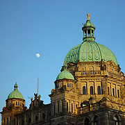 The nearly full moon rises over the Parliament Building in Victoria, British Columbia. The Parliament Building opened in 1898 and features a gilded bronze statue of Captain George Vancouver, whom Vancouver Island is named for.