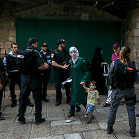 A Palestinian woman and her children walks through police officers along the Hagai&nbsp;Street&nbsp;in Jerusalem's Old City  on after the two attacks, the street turned into a security area, with about 10 checkpoints and hundreds of police posted along it. Most of the Palestinian merchants closed their stores, waiting for the rage to pass.<br /> Photo by Olivier Fitoussi.
