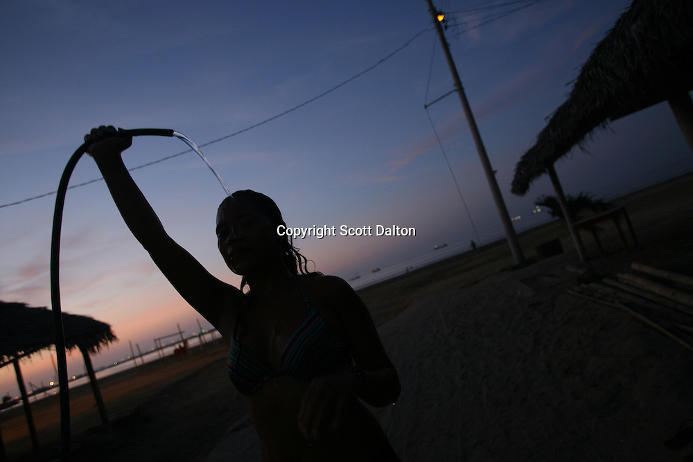 A young woman uses a hose to wash herself on a beach in Manta, Ecuador on April 14, 2008. Currently the United States uses an air base in Manta to conduct drug-trafficking surveillance flights. The United States military presence helps to contribute an estimated $6.5 million annually to the local economy, but the Ecuadorian government is looking into the possibility of closing the US base once the lease runs out in 2009. (Photo/Scott Dalton).