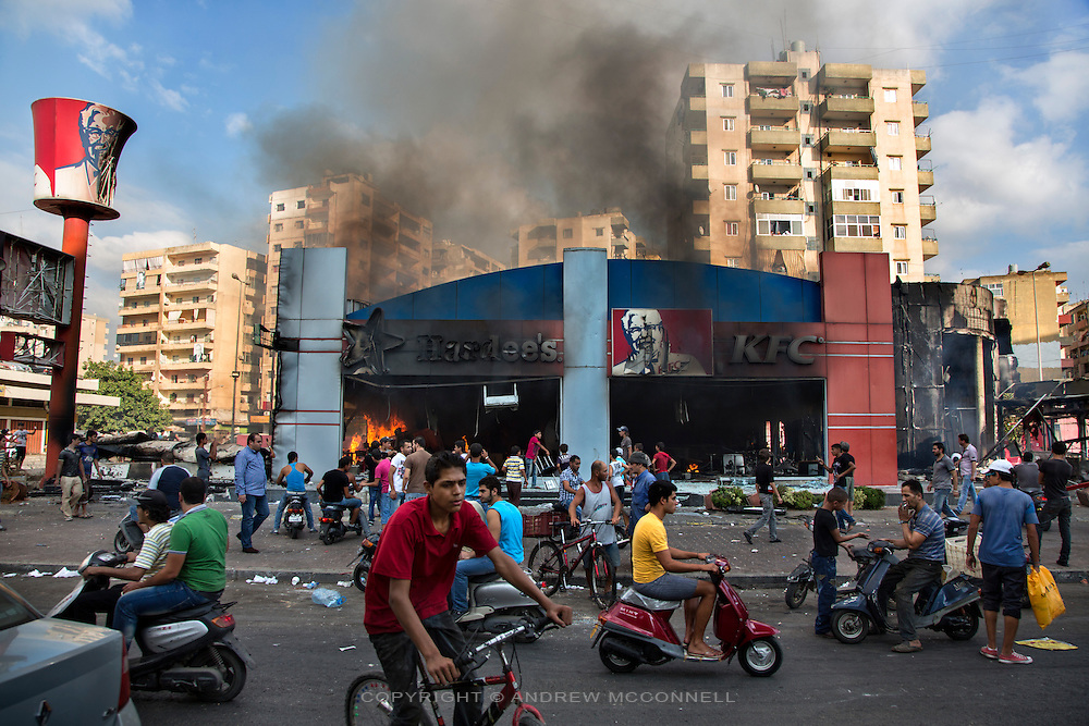 "A KFC and Hardee's restaurant burn after riots break out in Tripoli, Lebanon. The riots were in response to an anti-Islam film, ""Innocence of Muslims,"" that originated in the U.S. Extremists elements have grown in Lebanon's second biggest city in recent years with Salafists playing an increased military role there."