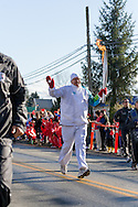 Torch runner Keary Bott runs along Fraser Highway during the 2010 Olympic Winter Games Torch Relay.  Photographed in Langley (Aldergrove), British Columbia, Canada.