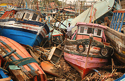 Exhausted fishermen who lost their homes, boats and livelihoods try to salvage what they can from decimated boats after the tsunamis ravaged the coast of India, Africa and Asia January  23, 2005 in Nagapattinum, Tamil Nadu, India.
