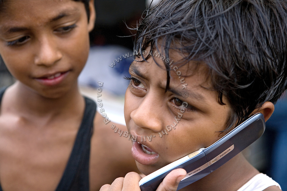 Azharuddin Ismail, 10, the child actor playing the role of 'young Salim', the brother of Jamal, protagonist of Slumdog Millionaire, the famous movie winner of 8 Oscar Academy Awards in December 2008, is chatting on his mobile phone near a friend in the slum where he still lives with his family next to the train station of Bandra (East), Mumbai, India. Various promises were made to lift the two young actors (Azharuddin Ismail and Rubina Ali) from poverty and slum-life but as of the end of May 2009 anything is yet to happen. Rubina's house was recently demolished with no notice as it lay on land owned by the Maharashtra train authorities and she is now permanently living with her uncle's family in a home a stone-throw away in the same slum. Azharuddin's home too was demolished in the past two weeks, as it happens every year in his case, because the concrete walls were preventing local authorities to clear a drain passing right behind it. As usual, his father is looking into restoring the walls as soon as the work on the drain has been completed.