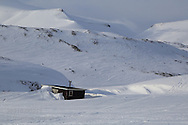 Snow-bound mountain hut in April between Longyearbyen and Barentsburg; Svalbard, Norway.
