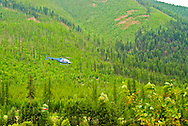 Helicopter scoops water with bucket from Kootenai River to fight forest fire in Kootenai National Forest Montana