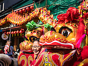 27 JANUARY 2017 - BANGKOK, THAILAND: A Chinese tourist poses for a photo with Chinese Lion dancers at a Chinese Shrine in Bangkok on Chinese New Year. 2017 is the Year of the Rooster in the Chinese zodiac. This year's Lunar New Year festivities in Bangkok were toned down because many people are still mourning the death Bhumibol Adulyadej, the Late King of Thailand, who died on Oct 13, 2016. Chinese New Year is widely celebrated in Thailand, because ethnic Chinese are about 15% of the Thai population.       PHOTO BY JACK KURTZ