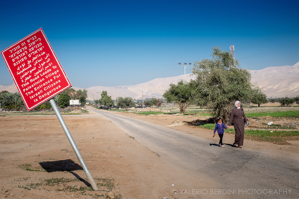A woman and her daughter walk out the Area A delimiting a West Bank territory under Palestinian Authority control. A sign alerts Israeli citizens of the danger entering such areas. Area A covers circa 3% of the West Bank, This area includes eight Palestinian cities and their surrounding areas with no Israeli settlements. Entry into this area is forbidden to all Israeli citizens. The Israel Defense Forces occasionally enters the area to conduct raids to arrest suspected militants.