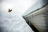 """JEROME A. POLLOS/Press..Mark McClain clears the snow from the roof of an elderly couple's home Wednesday  in Kellogg. """"I don't need a gym, I got aerobics on a roof,"""" McClain said. The 45-year-old has been spending the last 10 days clearing roofs of businesses and homes."""