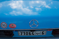 The sky is reflected in a Moroccan taxi, a Mercedes.