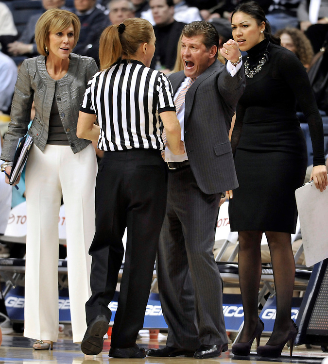 Connecticut head coach Geno Auriemma argues a call with an official as associate head coach Chris Dailey, left, and assistant coach Marisa Moseley, right, looks on during the first half of an NCAA college basketball game against Notre Dame, in Storrs, Conn., Saturday, Feb. 19, 2011. (AP Photo/Jessica Hill)