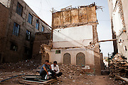 Kashgar: Young Uighur men salvage remnants of a recently demolished Uighur house in the old city of Kashgar...Despite the migration of millions of Han Chinese to the western part of the Xinjiang Uighur Autonomous Region, the Uighur community continue to practice their muslim culture and resist the suppression of their cultural and religious traditions by the Chinese government....The chinese government has been criticised for the redevelopment of the old city, which has involved the destruction of many of the old houses in the town that were built without regulation, officials claiming them to be overcrowded and uncompliant with earthquake codes...Many in the chinese government believe Kashgar to a breeding ground for Uighur separatists, who Beijing claim to have links to terrorism...The european parliament has called for a halt to the cultural destruction of Kashgar, suggesting that Kashgar be added tot he UNESCO World heritage 'Silk Road' project, and calling on the chinese government to develop a genuine Han-Uighur dialogue to adopt more inclusive and comprehensive economic policies in Xinjiang in order to protect the cultural identity of the Uighur population..©JTanner/July 2011