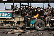 A man lights a cutting torch at Dinko Valev's junkyard in Yambol, Bulgaria. This man, a Roma, single-handedly breaks down the stripped busses in to scrap metal with a torch.<br /> <br /> Matt Lutton / Boreal Collective for VICE
