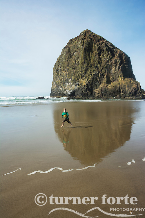 Toddler boy runs along beach in front of Haystack Rock on Cannon Beach, Oregon.