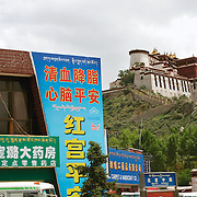 The Potala Palace, surrounded by Chinese businesses, Lhasa, Tibet. 8/4/05. It was historically the seat of the Tibetan Government and was the primary residence of the Dalai Lama until 1959, when the 14th Dalai Lama fled to Dharamsala after a failed uprising..Today the Potala Palace is a state museum, a popular tourist attraction, and a UNESCO World Heritage Site.