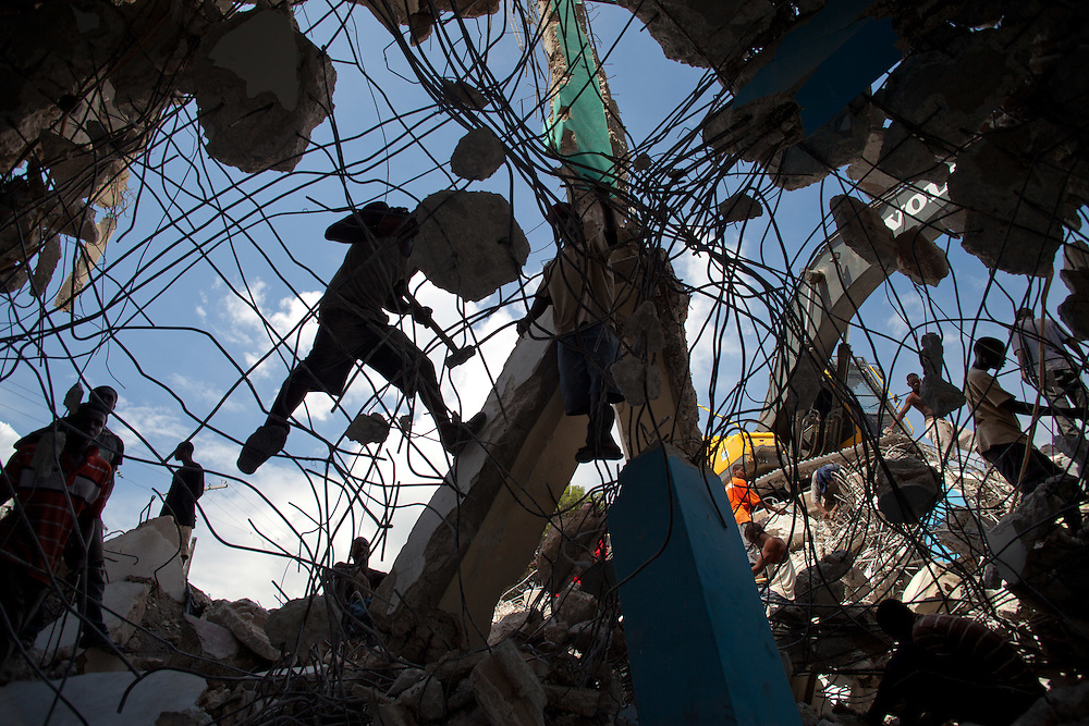 Men breakup rubble, from the January 12th earthquake, with hammers to retrieve scrap metal to resell.