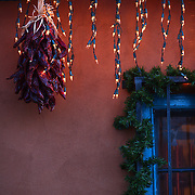 SHOT 12/26/2007 - A chile ristra and Christmas lights hang on the side of a store in Old Town Albuquerque. The area is a historic district in Albuquerque, New Mexico, dating back to the founding of the city by the Spanish in 1706. Today it is a popular shopping and tourist destination. Old Town comprises about ten blocks of historic adobe buildings grouped around a central plaza (a common feature of Spanish colonial towns). Many of the buildings in Old Town are houses that have been converted into restaurants and small art and souvenir shops. Albuquerque is the largest city in the state of New Mexico, United States. It is the county seat of Bernalillo County and is situated in the central part of the state, straddling the Rio Grande. The city population was 448,607 as of the 2000 U.S. census. As of the 2006 census estimate, the city's population was 504,949, with a metropolitan population of 816,811 as of July 1, 2006. In 2006, Albuquerque ranked as the 33rd-largest city and 61st-largest metropolitan area in the U.S. Albuquerque is home to the University of New Mexico (UNM) and Kirtland Air Force Base as well as Sandia National Laboratories and Petroglyph National Monument. The Sandia Mountains run along the eastern side of Albuquerque and the Rio Grande flows through the city north to south..(Photo by Marc Piscotty/ © 2007)