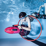 Boy with an underwater scooter steering through a hoop