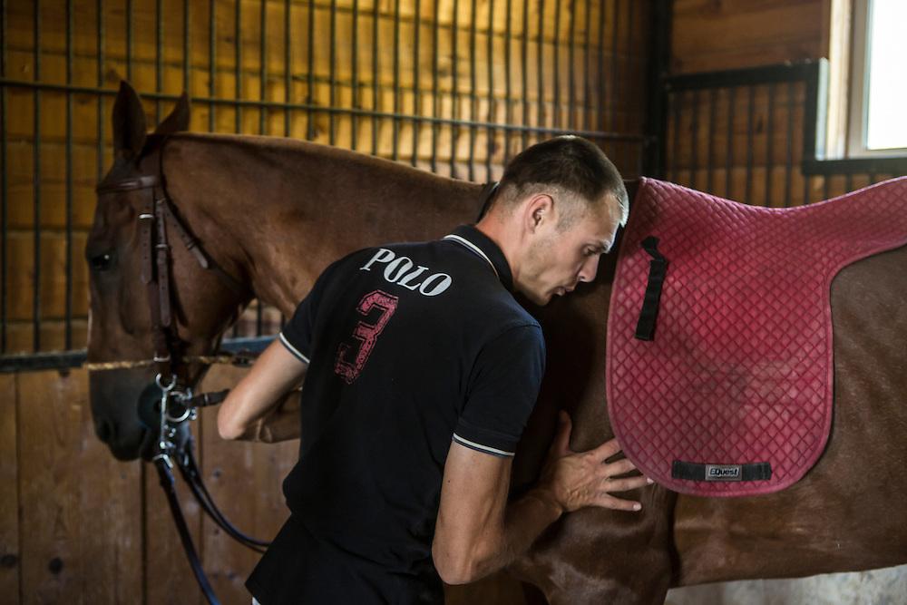Aleksander Dzarko prepares to ride one of Potapovo Farm's polo horses on Sunday, August 18, 2013 in Potapovo, Russia.