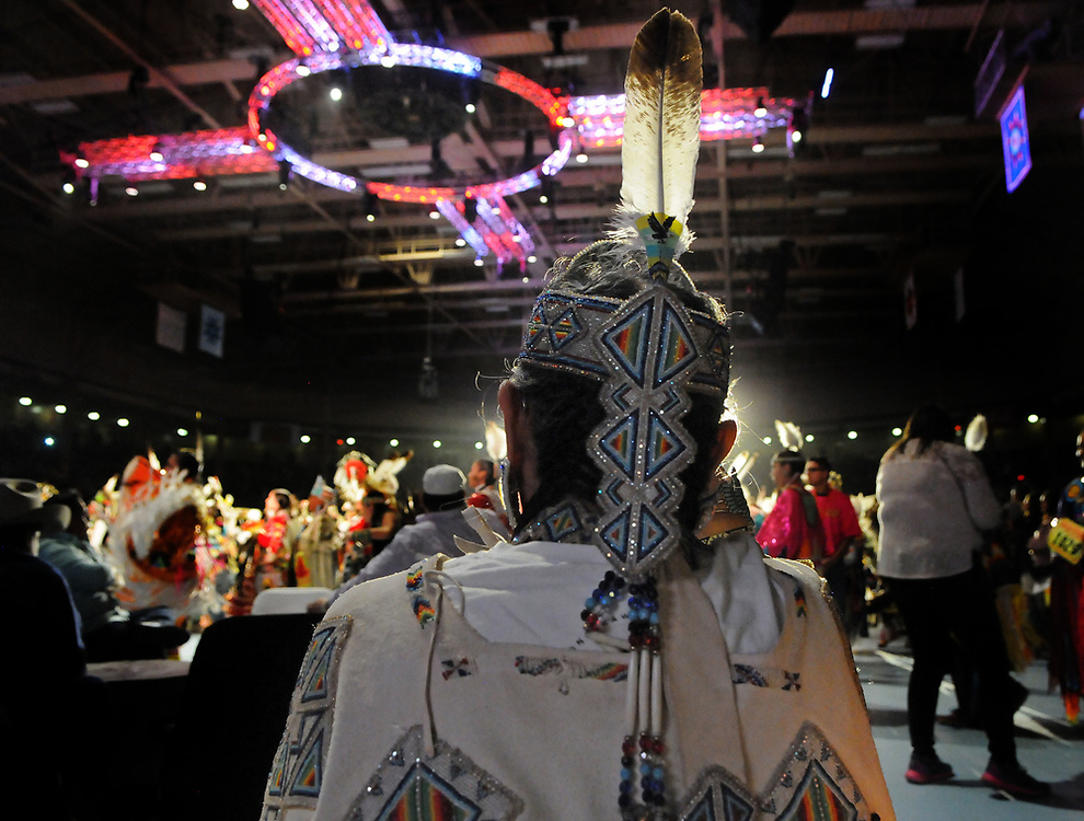 jt042817u/a sec/jim thompson/ A women watches the Grand Entrance of the  2017 Gathering of Nations Pow-Pow.  Friday April 28, 2017. (Jim Thompson/Albuquerque Journal)