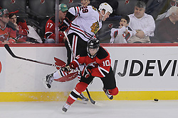 Mar 27; Newark, NJ, USA; New Jersey Devils defenseman Peter Harrold (10) hits Chicago Blackhawks left wing Bryan Bickell (29) during the third period at the Prudential Center. The Devils defeated the Blackhawks 2-1 in an overtime shootout.
