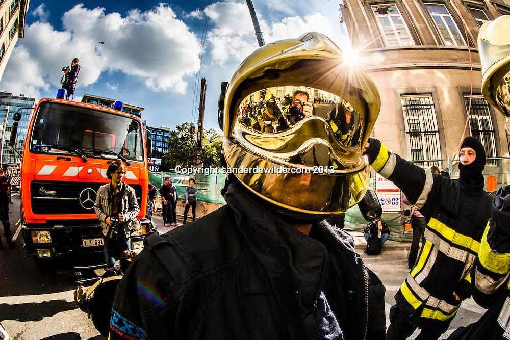 Verschillende brandweerkorpsen voeren actie tegen bezuinigingen in het centrum van Brussel bij de ambstwoning in de Wetstraat van de minister president.Brandweerman met gouden vizier masker
