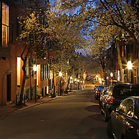 Romantic Boston cityscape photography of old colonial brick row houses along lantern lit street in Beacon Hill on a beautiful spring night. Cherry blossom blowing in the wind while the lanterns provide the warm city street night light in Beacon Hill.<br />