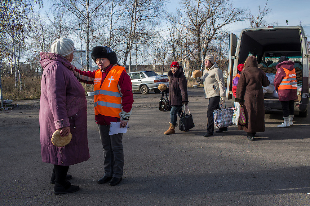 A church member prays with a woman while other volunteers from the Good Word Protestant Church distribute bread to local residents in need on Thursday, December 10, 2015 in Mariinka, Ukraine.