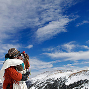 LOVELAND SKI AREA, CO - FEBRUARY 14: Elaine Vardamis (right) of Nederland, Co. kisses her husband Dan Vardamis after the couple renewed their vows at Loveland Ski Area in Colorado at the 20th Annual Marry Me & Ski Free Mountaintop Matrimony on Valentine's Day Monday, February 14th. The mass wedding ceremony was held at noon at 12,050 feet outside of the Ptarmigan Roost Cabin at Loveland. More than 75 couples were pre-registered to get married or renew their vows high on The Continental Divide in this yearly Loveland tradition.  Following the ceremony couples were invited to a casual reception complete with a champagne toast, wedding cake and music. The couple was married about eight months ago at the County Clerks office in Boulder, Co. and this was their first official ceremony. (Photo by Marc Piscotty © 2011)